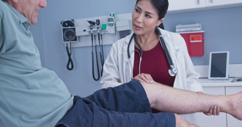 Man's knee being examined by female doctor
