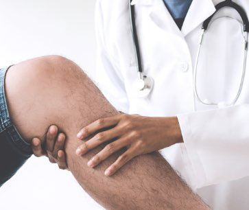 Doctor looking at a man's knee